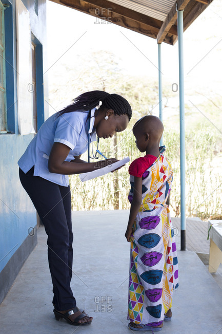 Nurse examining young girl in clinic in Kenya, Africa