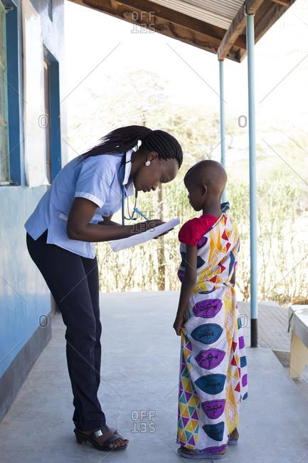 Nurse examining young girl in clinic in Kenya, Africa