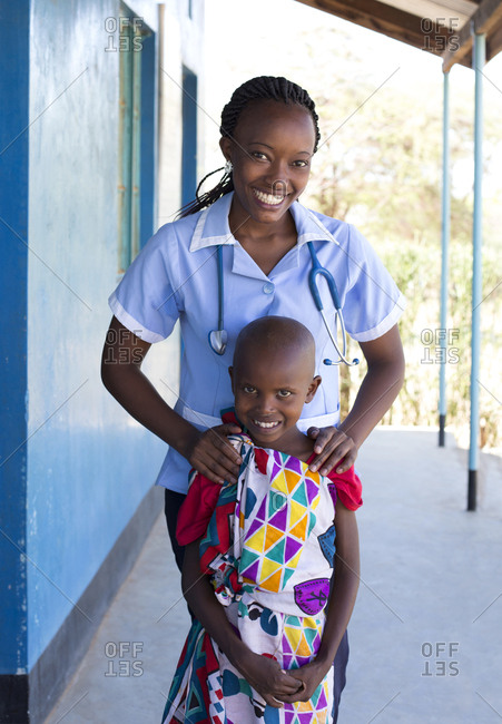 Portrait of a nurse standing with a young girl in clinic in Kenya, Africa