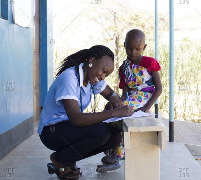 Kenya, Africa - April 25, 2017: Nurse examining young girl in clinic