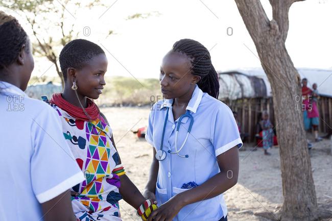 Nurses examining patient in rural village in Kenya, Africa