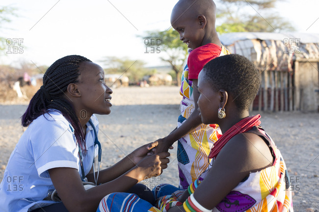 Nurse examining mother and daughter in rural village in Kenya, Africa