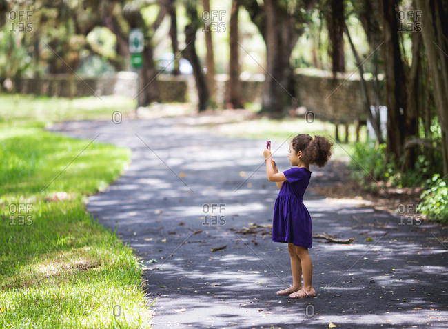 Little girl takes a nature photo