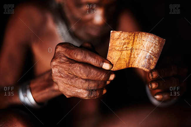 Kunene, Namibia - March 20, 2016: A portrait of a Himba village elder holding his old identification card from the former country of Southwest Africa