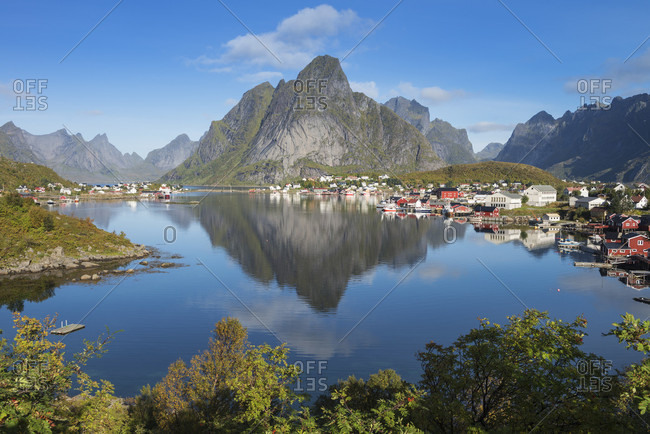 Lofoten Islands, Norway - September 15, 2016: Reflection of Olstind mountain peak in Reine harbor