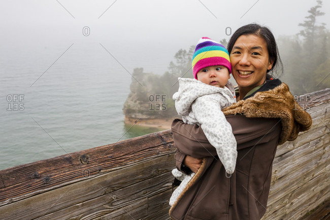 Portrait of mother holding baby daughter at Pictured Rocks National Lakeshore outlook