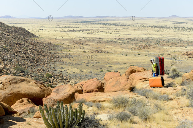 A man walking with his crash pads Bouldering expedition in Namibia Africa