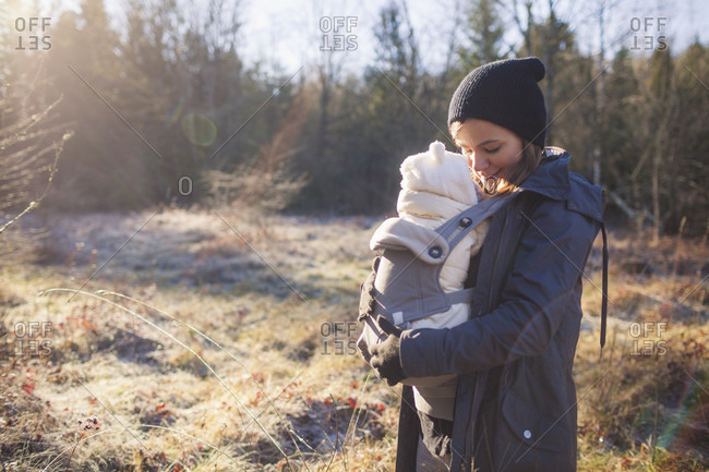 A mother keeps her newborn warm while walking in a park