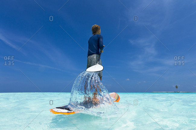 A surfer stand up paddling in the main lagoon of Gili Lanjanfushi, in the Maldives