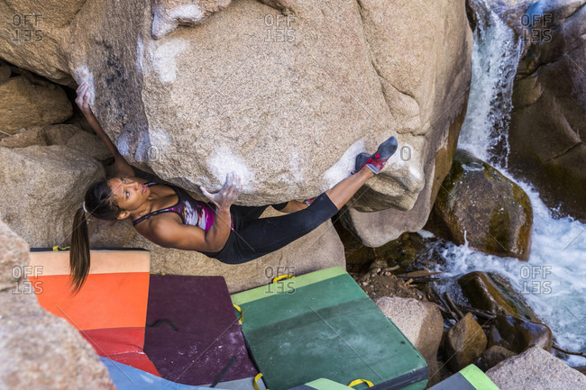 A strong female climbs on an overhanging boulder by a river in Colorado