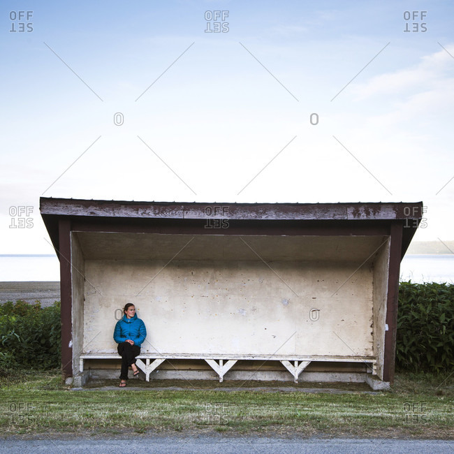 A woman sits alone in a covered buss top with water in the distance