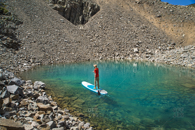 A young male paddleboarding on a small alpine lake in the Colorado backcountry