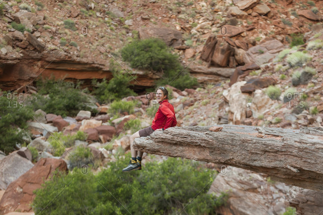 A woman tests her courage on an overhanging rock flake in Jasper Canyon, Canyonlands National Park, Utah