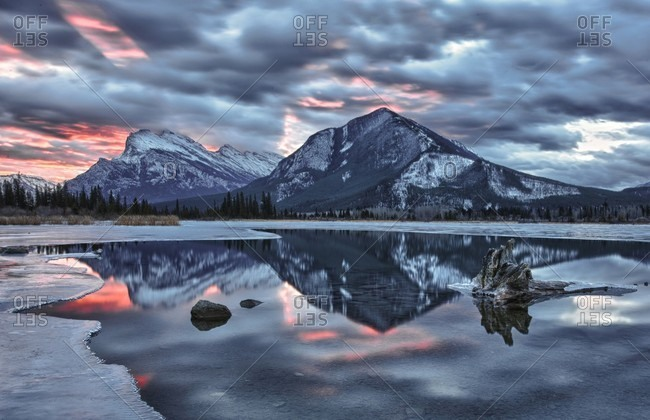 Mountain reflected in lake at sunrise, winter