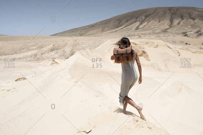 Woman walking on sand dune