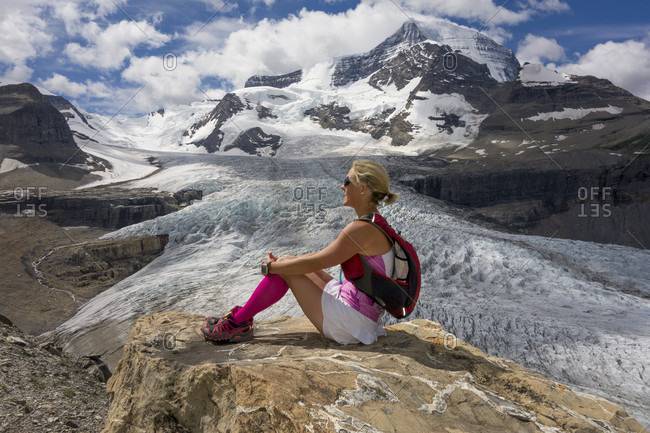 Woman trail runner relaxes on rock, mountains