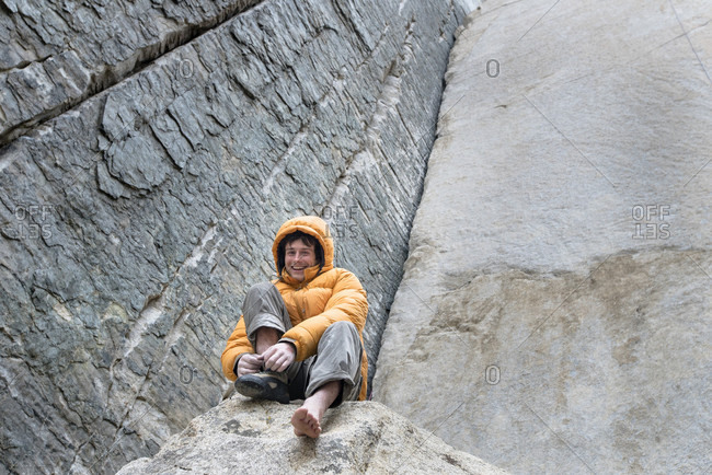 Young male climber putting shoes on in preparation for climbing on Pratts Crack