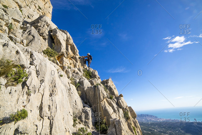 A man rock climbing high on the peak of Puig Campana above the city of Benidorm, Alicante Region, Costa Blanca in Mediterranean Spain