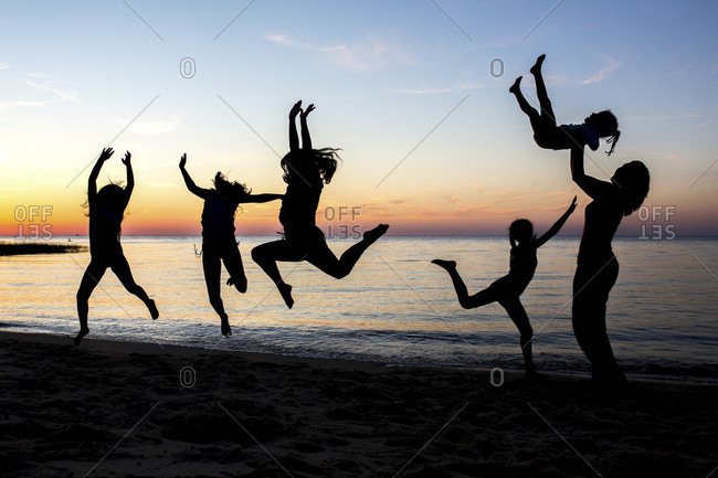 People are silhouetted jumping on a beach on Cape Cod