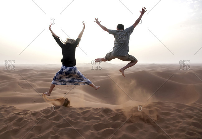 People jump in the Chegaga dunes in the Sahara desert in Morocco