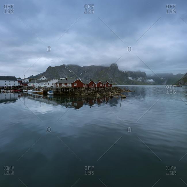 Coastal cabins resting on poles near waterside