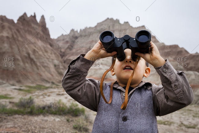 Boy wearing explorer costume holding binoculars
