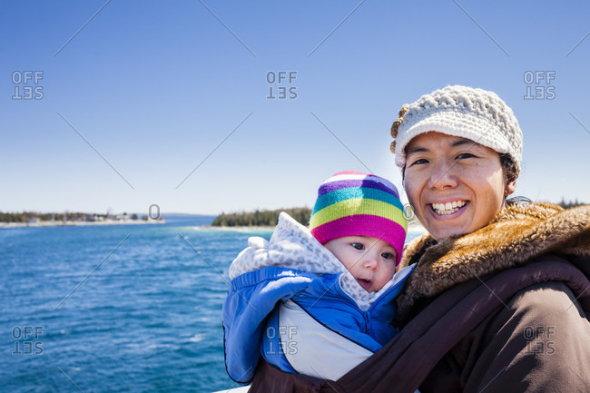 Portrait of mother holding baby daughter outdoors
