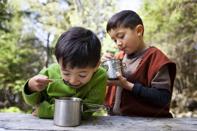 Two boys eating from metal mugs in Bruce Peninsula National Park