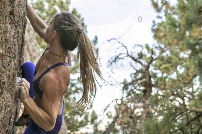 Strong female climber on outdoor boulder in Colorado