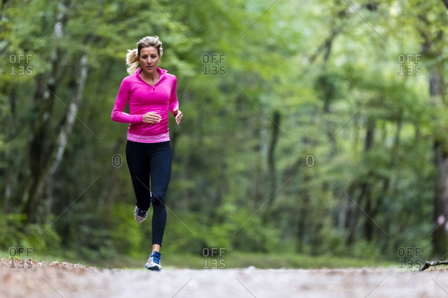 Woman in pink sweatshirt running along road in forest