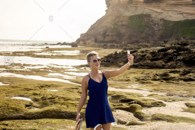 Woman taking selfie on coastline
