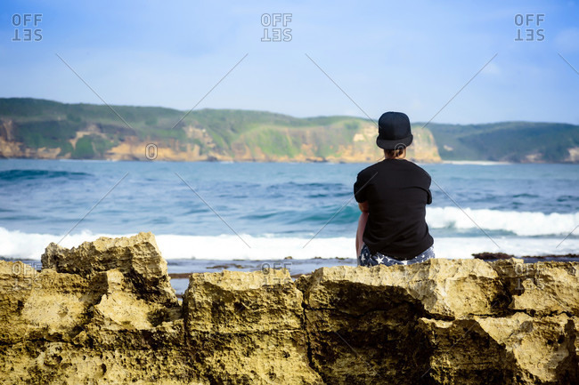 Woman sitting on coastline, contemplating view