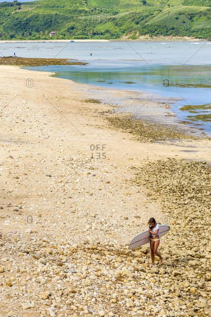 Female surfer walking on beach