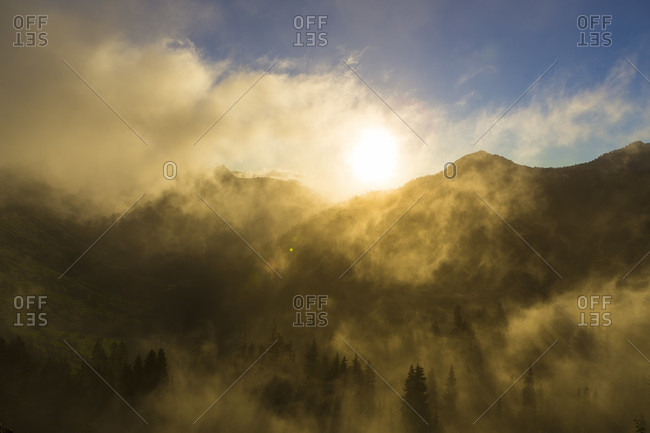 The sun shines through wispy clouds as it rises over a mountain range
