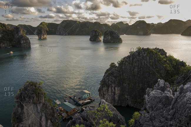 A group of floating houses nestles below limestone towers in Halong Bay, Quang Ninh Province