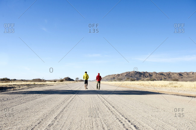 Two man walking on a track in the middle of nowhere , Namibia, Africa