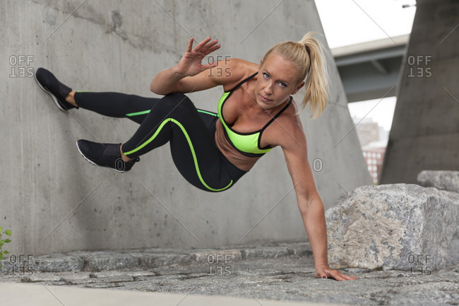 Fit Blonde Woman Doing An Abs Crunch Against A Wall Outdoors In The City