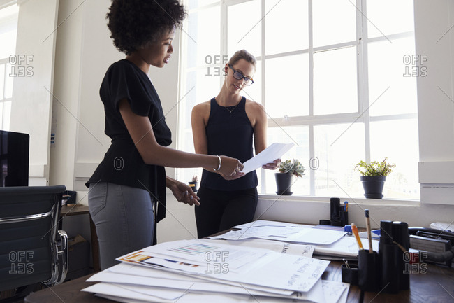 Two young businesswomen stand working together in an office