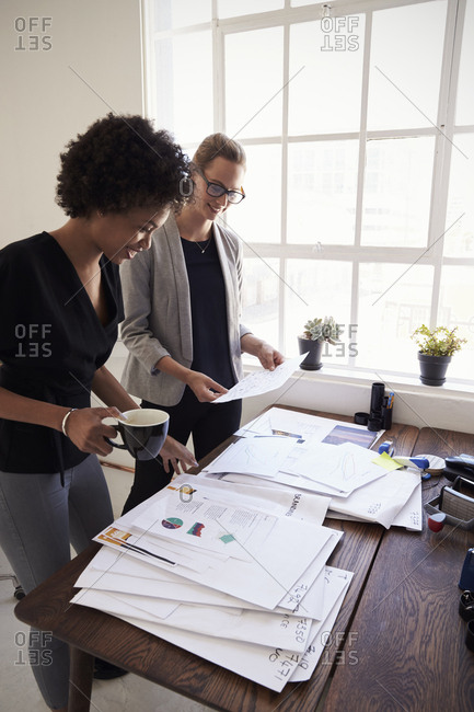 Two happy businesswomen working together in office