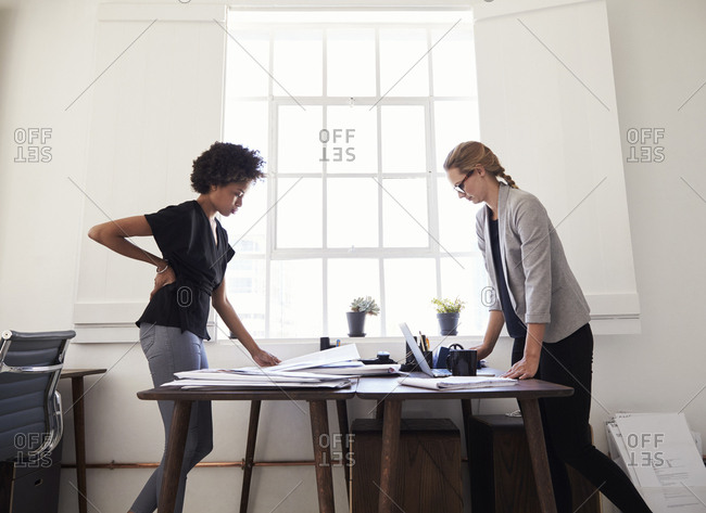 Two women stand working at opposite sides of an office desk