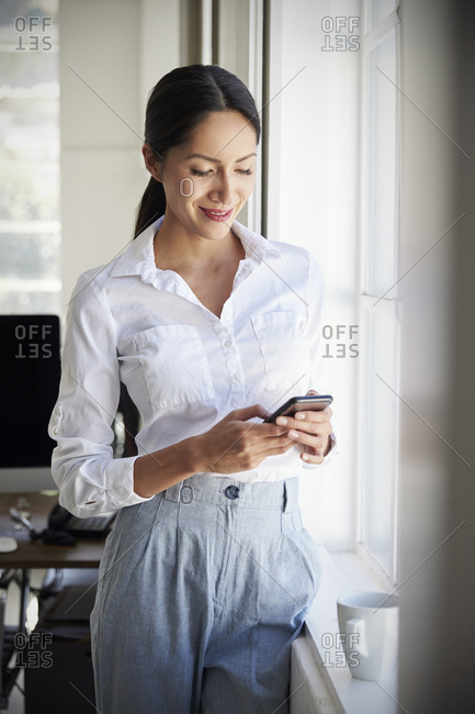 Happy Asian businesswoman using phone in an office