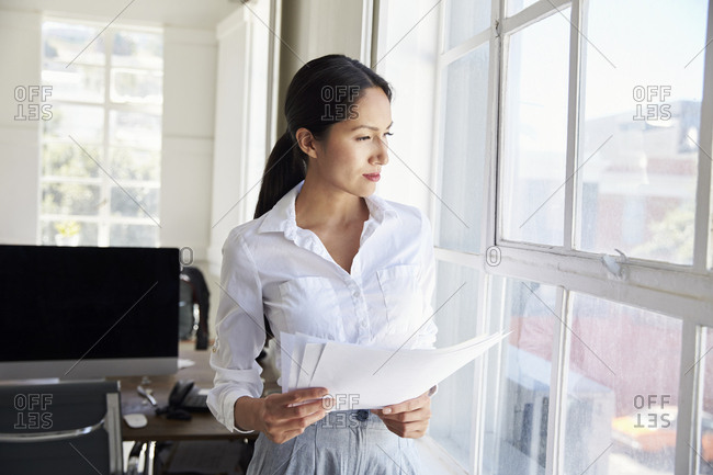 Young businesswoman holding papers looking out of window