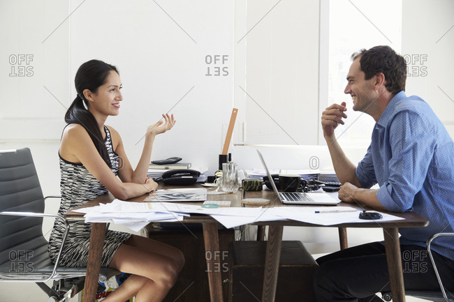 Two happy business colleagues sit talking at desk