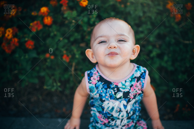 Toddler making smiling face by flowers
