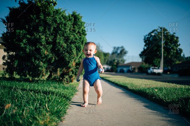 Excited toddler walking on sidewalk