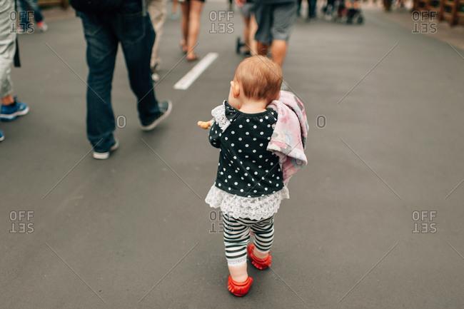 Toddler walking in street cradling doll