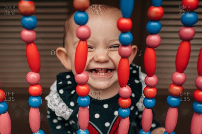 Toddler girl grinning through beads