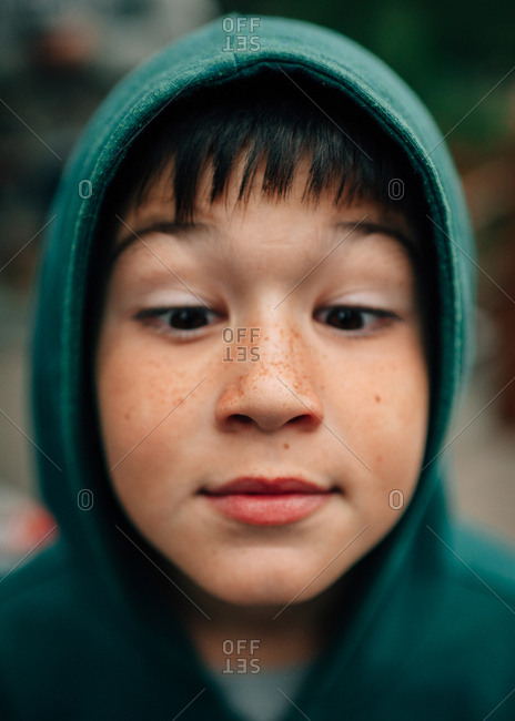 Boy in hoodie crossing his eyes