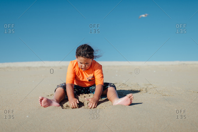 Girl alone digging in sand