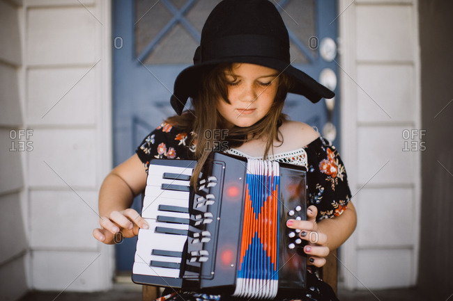Girl on porch playing an accordion